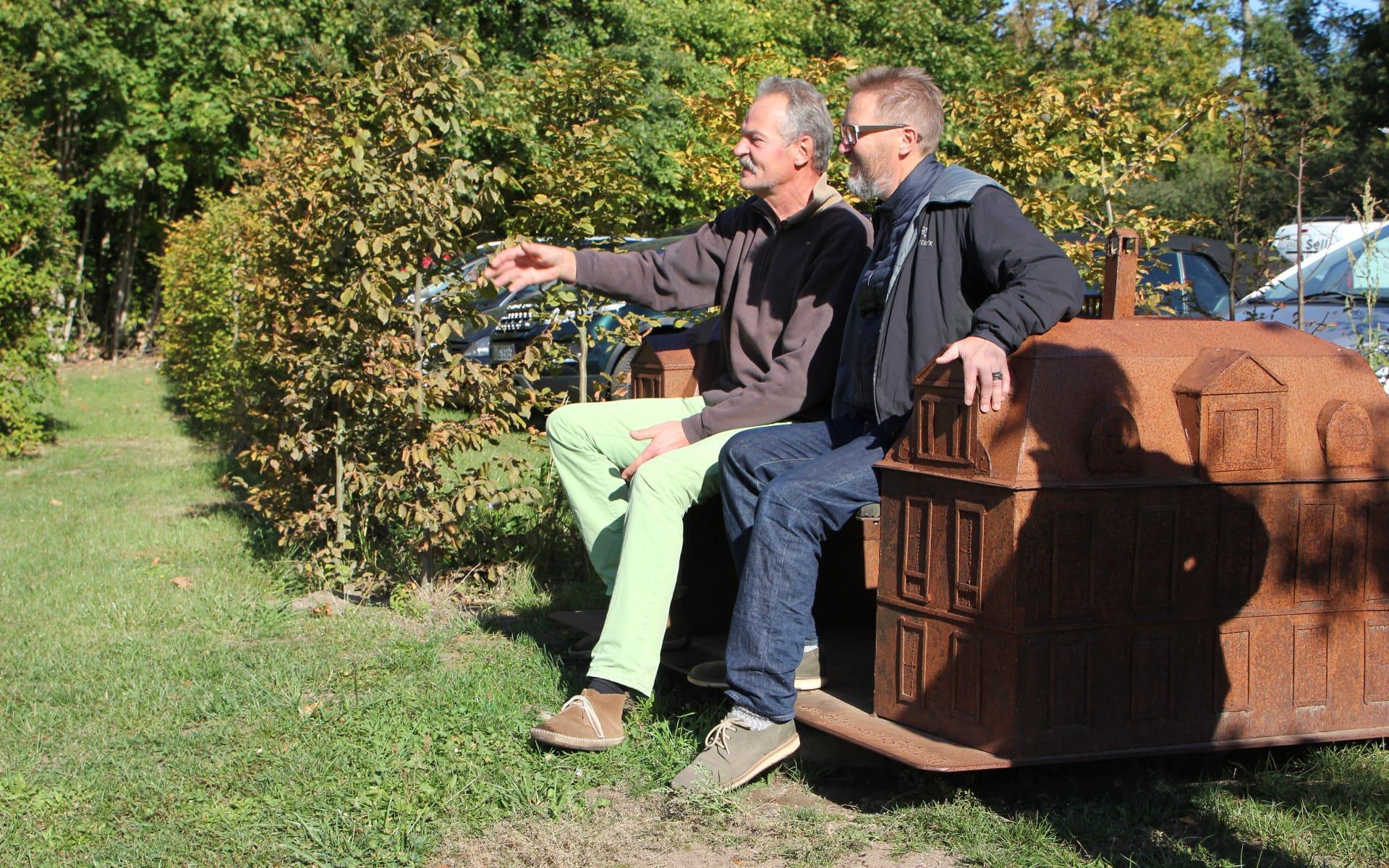 Kunsttour Karwe - Zwei Gäste auf einer Bank in Gestalt eines Schloss im Garten