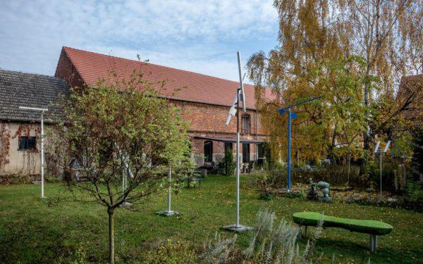 Kunsttour Betzin-Brunne - Die Skulpturen im Garten und Werkstatt im Hintergrund